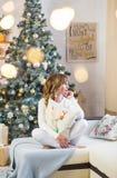 De mooie jonge vrouw in wit met grote Kerstmis stelt voor stock afbeelding