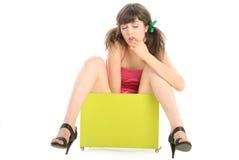 De mooie jonge vrouw zit in doos Stock Fotografie