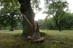De mooie jonge vrouw zit onder een boom Stock Foto
