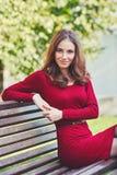De mooie jonge vrouw zit op een bank Royalty-vrije Stock Foto