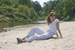 De mooie jonge vrouw zit op het zandige strand Stock Afbeeldingen