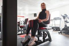 De mooie jonge vrouw in zwarte sportkleding in gymschoenen zit op een moderne simulator in de gymnastiek Het meisje schudt haar b royalty-vrije stock afbeeldingen