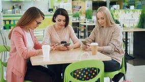 De mooie jonge vrouwen gebruiken smartphones zitting bij lijst in koffie en bekijken de schermen Moderne technologie, de jeugd stock videobeelden