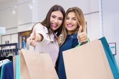 De mooie jonge vrouwen met het winkelen zakken het tonen beduimelt omhoog Royalty-vrije Stock Afbeeldingen