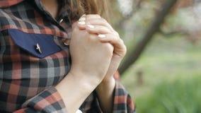 De mooie jonge vrouwendraaien aan God met gevoel in gebed, het meisje vouwden haar wapens bij haar borst en met dankbaarheid beki stock footage