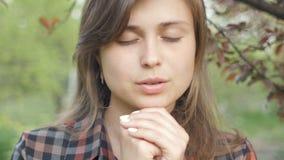 De mooie jonge vrouwendraaien aan God met gevoel in gebed, het meisje vouwden haar wapens bij haar borst en met dankbaarheid beki stock videobeelden