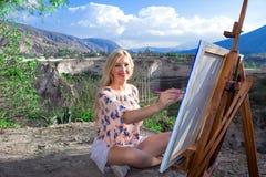 De mooie jonge vrouwenkunstenaar schildert een landschap in aard Het trekken op de schildersezel met kleurrijke verven in openluc royalty-vrije stock afbeelding