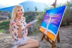 De mooie jonge vrouwenkunstenaar schildert een landschap in aard Het trekken op de schildersezel met kleurrijke verven in openluc stock afbeelding