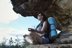 De mooie jonge vrouwenwandelaar geniet van de mening over bergbovenkant Stock Foto