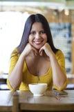 De mooie jonge vrouwenzitting in een koffiewinkel en drinkt thee Stock Foto's