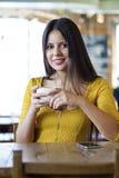 De mooie jonge vrouwenzitting in een koffiewinkel en drinkt thee Stock Afbeelding