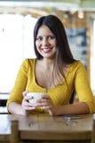 De mooie jonge vrouwenzitting in een koffiewinkel en drinkt thee Stock Foto