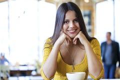 De mooie jonge vrouwenzitting in een koffiewinkel en drinkt thee Stock Fotografie