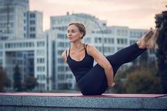 De mooie jonge yoga van vrouwenpraktijken Variatie van Navasana met draai - de boot stelt in openlucht tegen de achtergrond van m stock foto's