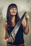 De mooie jonge zaag van de meisjesholding over grunge Royalty-vrije Stock Fotografie