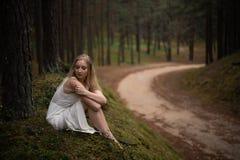 De mooie jonge zitting van de blondevrouw in bosnimf in witte kleding in altijdgroen hout royalty-vrije stock foto's
