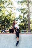 De mooie jonge zitting van het hipstermeisje op de rand van een helling royalty-vrije stock afbeelding