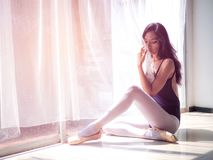 De mooie jonge zitting van de vrouwenballetdanser op de vloer royalty-vrije stock foto