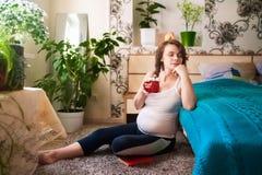 De mooie jonge zwangere vrouw zit thuis in een wit mouwloos onderhemd en sportenbeenkappen en drinkt cacao met een heemst, stock afbeelding