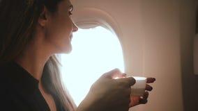 De mooie jongelui ontspande gelukkige Europese toeristenvrouw die van hete drank genieten en zonlichtmening over de zetel van het stock footage