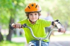 De mooie jongen berijdt cyclus stock foto