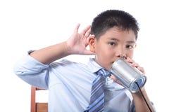 De mooie jongen luistert de telefoon van het tinblik Stock Afbeelding