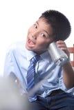 De mooie jongen luistert de telefoon van het tinblik Royalty-vrije Stock Afbeeldingen