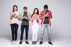 De mooie jongeren gebruikt gadgets en het glimlachen, zich bevindt tegen witte bakstenen muur royalty-vrije stock afbeelding