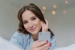 De mooie Kaukasische die vrouw luistert audio met oortelefoons, aan modern slim telefoonapparaat worden aangesloten, horlogesvide royalty-vrije stock foto's