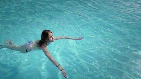 De mooie Kaukasische model, jonge vrouw zwemt in een pool met blauw water in een hotel, onder de open hemel Het concept stock footage