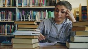 De mooie Kaukasische tienervrouw zit bij lijst in de universitaire digitale tablet van de bibliotheekholding Zij is vermoeid en stock videobeelden