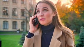 De mooie Kaukasische vrouw heeft telefoongesprek, gelukkig sprekend terwijl het status van geïsoleerde ontspannen openlucht zijnd stock footage