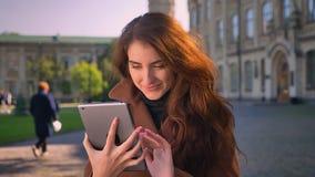 De mooie Kaukasische vrouw jat haar tablet, dan tonend het groene scherm bij camera en als tekendemonstraties met stock videobeelden