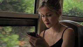 De mooie Kaukasische vrouwelijke toerist berijdt de metro Gebruikt een mobiele telefoon keurig bekijkend hem die slingeren langza stock videobeelden