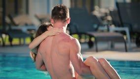De mooie kerel die de jonge vrouw op omcirkelen dient het zwembad in stock footage