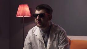 De mooie kerel met baard die zonnebril en witte laboratoriumlaag dragen verklaart materiaal stock video