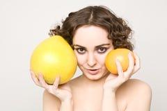 De mooie krullende grapefruit en de pompelmoes van de meisjesholding Royalty-vrije Stock Foto