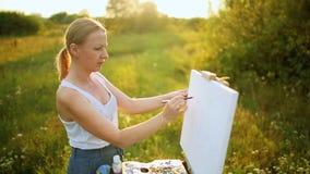 De mooie kunstenaar van de blondevrouw met een borstel in haar hand trekt op canvas in de aard stock videobeelden
