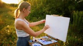 De mooie kunstenaar van de blondevrouw met een borstel in haar hand trekt op canvas in de aard stock video