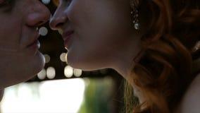 De mooie kus van het huwelijkspaar in de gloed van zonsonderganglicht in de stad stock video