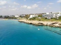 De mooie kustlijn van Cyprus, Middellandse Zee van turkooise kleur Huizen op de Mediterrane stad van de kusttoerist met een stran stock fotografie