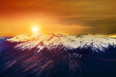De mooie landschapszon het toenemen hemel snowcaped over berg Royalty-vrije Stock Foto