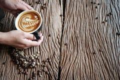 De mooie lattehanden worden gehouden op de oude houten vloer royalty-vrije stock foto's
