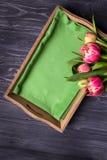 De mooie lente bloeit krullend tulpen en dienblad op een donkere achtergrond Hoogste mening Stock Afbeeldingen