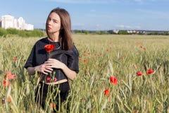 De mooie leuke jonge vrouw met volledige lippen met kort haar op een gebied met papaver bloeit in hun handen Royalty-vrije Stock Fotografie