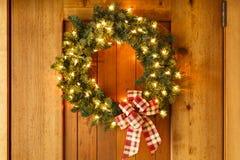 De mooie lichten van het huisdecoratie van de Kerstmiskroon op voordeur van huis stock afbeeldingen