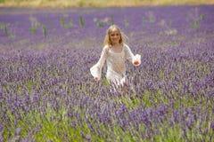 De mooie looppas van het blondemeisje door een lavendelgebied Royalty-vrije Stock Foto