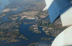 De mooie luchtmening van vliegtuigvleugel en de blauwe hemel betrekken over blauw oceaan en eiland Stock Afbeelding