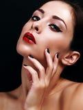 De mooie make-upvrouw met heldere rode lippen en de zwarte manicured Royalty-vrije Stock Afbeeldingen