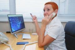 De mooie makelaar die van de meisjesvoorraad op de telefoon in het bureau spreken stock afbeeldingen